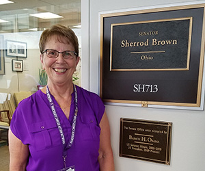 70s Caucasian female standing next to identifying name plate outside a senator's office