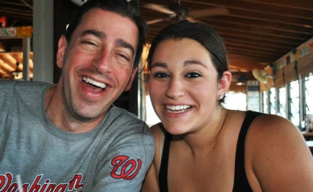 Father and daughter posing at a restaurant.