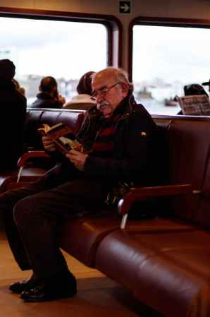 man in black jacket sitting on red leather chair