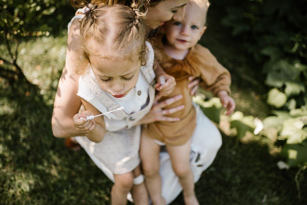 Mama przytula córki na urodzinowym pikniku w stylu boho