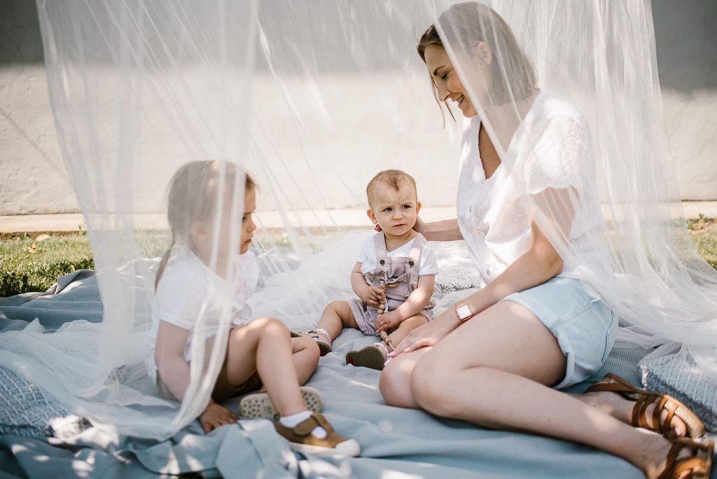 Mama z dziećmi siedzą na kocyku na pikniku boho