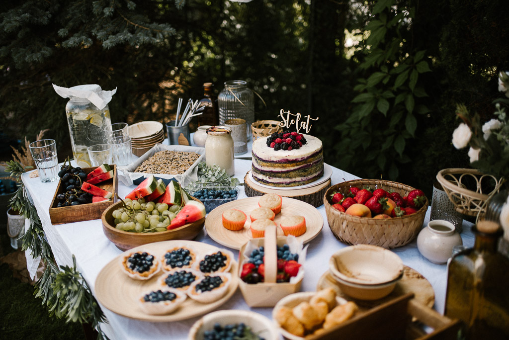 Szwedzki stół z tortem urodzinowym na przyjęciu w ogrodzie w stylu boho