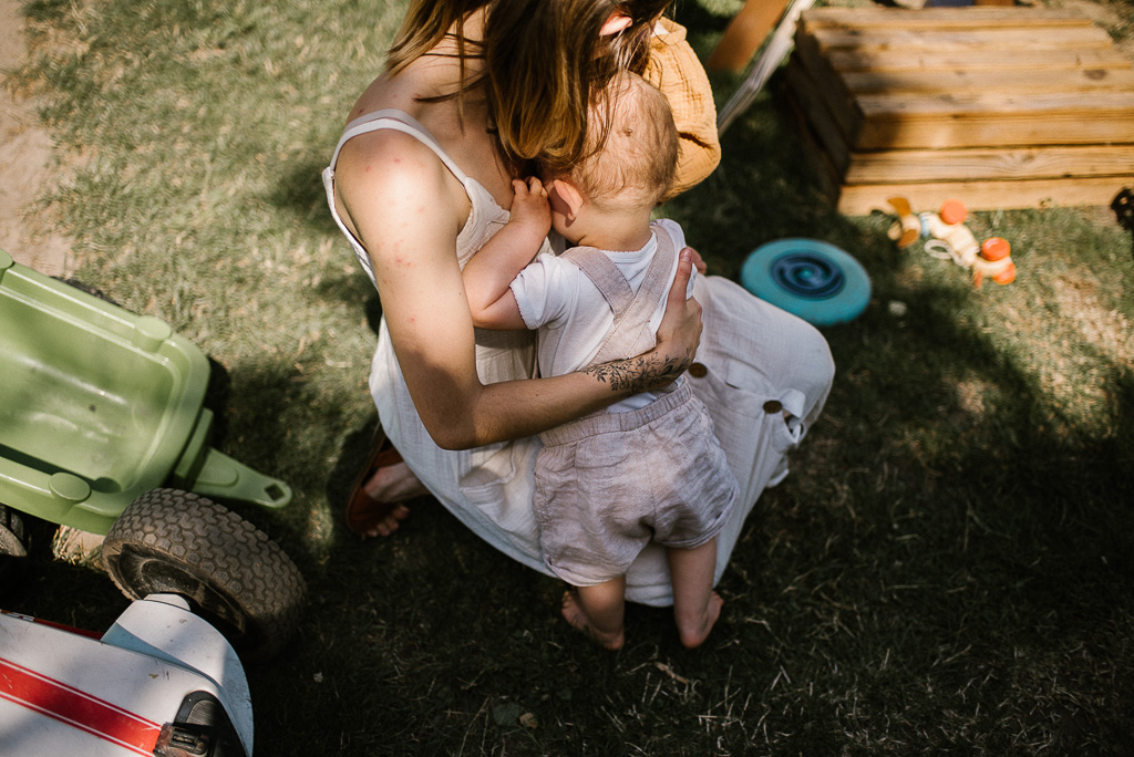 Zmęczona dziewczynka przytula się do mamy na urodzinowym pikniku boho