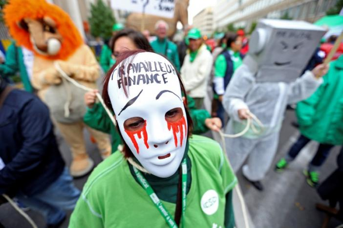 Woman wears mask during protest over the government's reforms and cost-cutting measures in Brussels