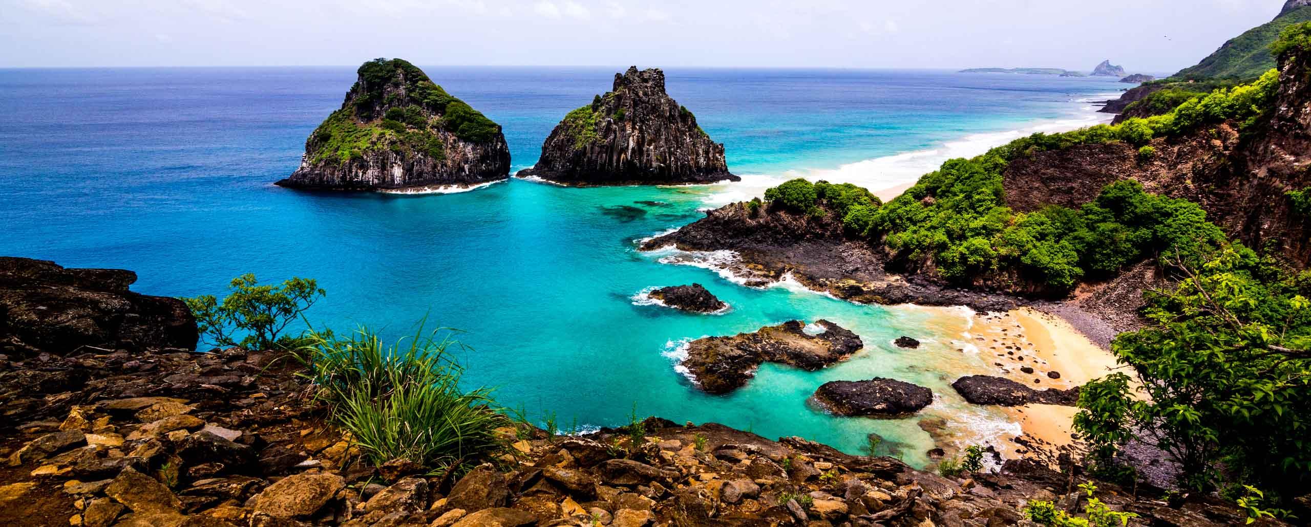 A visão da Praia dos Porcos e da Ilha Dois Irmãos no arquipélago de Fernando de Noronha com suas cores intensas ressaltadas pelo sol sobre o mar.