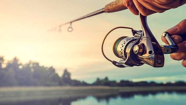 Mano con la canna da pesca che lancia l'amo nel lago