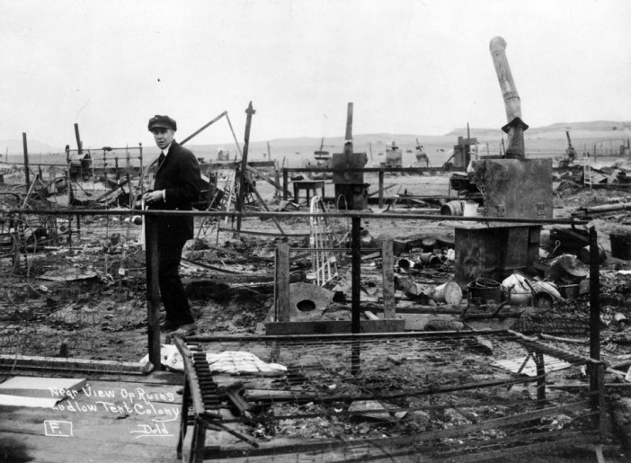 This 1914 photo provided by the Denver Public Library, Western History Collection, shows a man standing among the remains of a fire in Ludlow, Colo. April 20th marks the 100th anniversary of the Ludlow Massacre where 11 children and 2 women died in the fire set during a fight between striking coal miners and the Colorado National Guard. (Denver Public Library, Western History Collection)