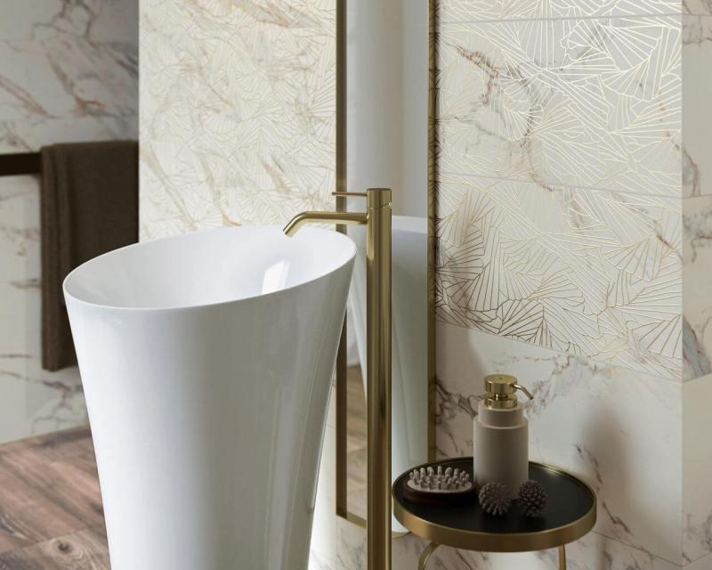 Wolnostojąca umywalka ijasne płytki zezłocistym motywem tworzą elegancką, szykowną łazienkę.
