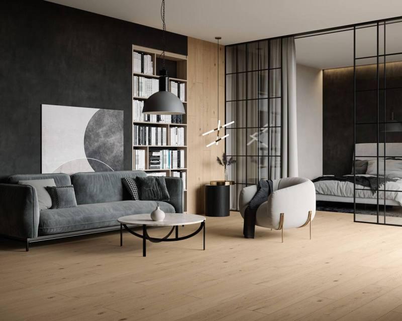Jasna podłoga orazprzeszklona ściana między salonem asypialnią torozwiązania, które wizualnie powiększają aranżowaną przestrzeń.