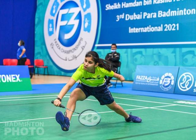 Young female badminton player with left arm impairment lunges for the shuttle