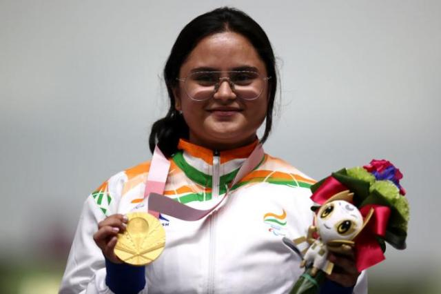 A young woman in the uniform of India posing with a gold medal
