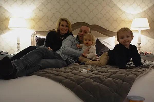 Saint-Valentin en famille, famille assise sur le lit avec les 2 enfants.