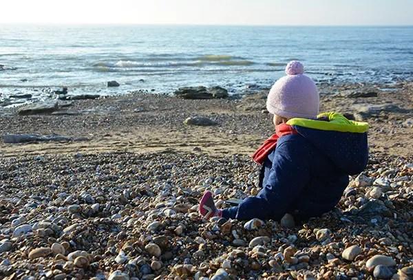 enfant sur la plage regardant la mer