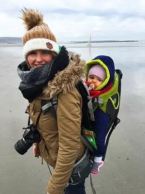 Côte d'Opale, maman voyageuse avec son enfant dans un porte bébé de randonnée