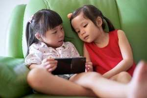 2 girls playing with smart device