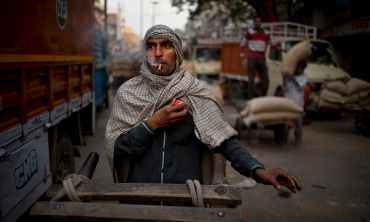 In this Wednesday, Nov. 26, 2014 photo, a cart puller smokes a beedi, tobacco rolled in an indigenously available leaf, as he waits for traffic to clear in New Delhi, India. Cart pullers who own their carts make $4-10 a day. (AP Photo/Saurabh Das)