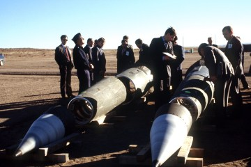 Soviet inspectors and their American escorts stand among several dismantled Pershing II missiles as they view the destruction of other missile components, 1989. [Wikimedia Commons]