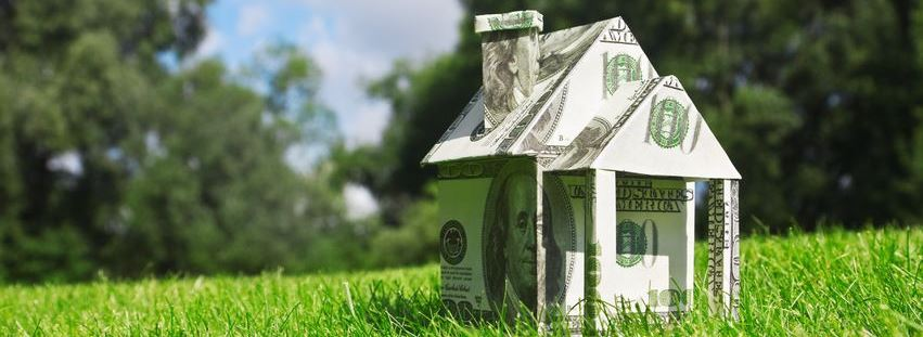 figure of a house made by dollar bills on the grass