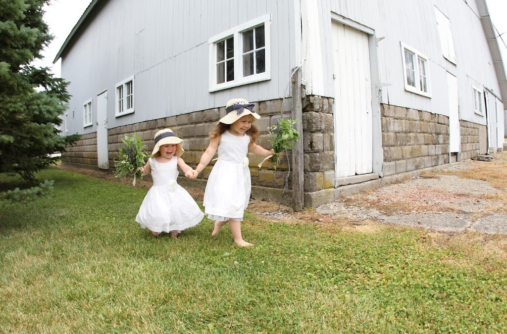 two little girls in white dresses with hats and bouquets