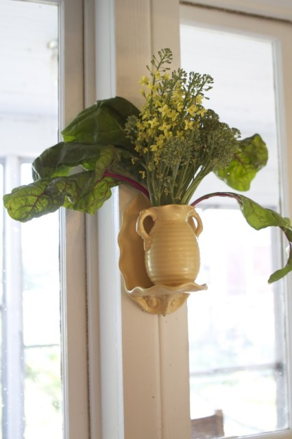 vase with broccoli flowers and chard leaves