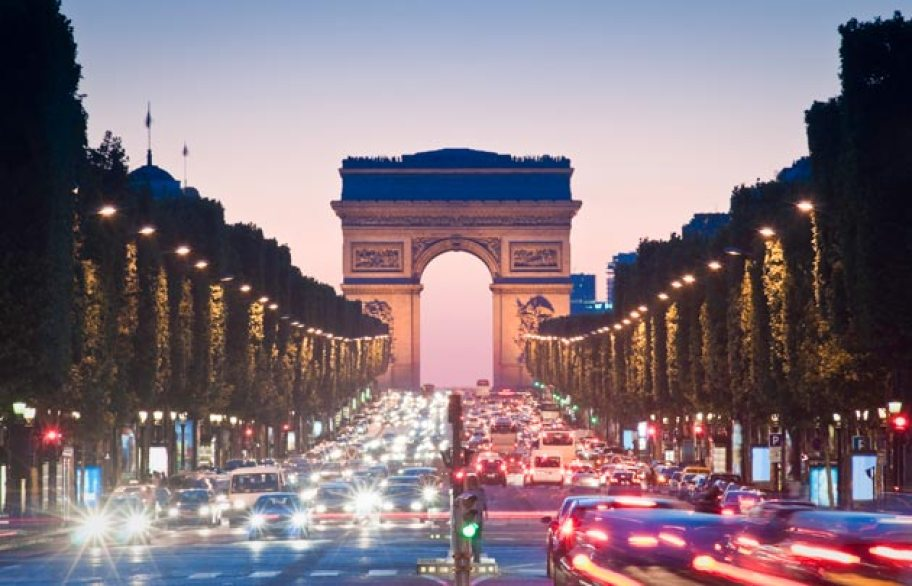 Road heading to Huge archway (Arc de Triomphe) with traffic and cars filling the streets - line of trees and lights guiding to Arch