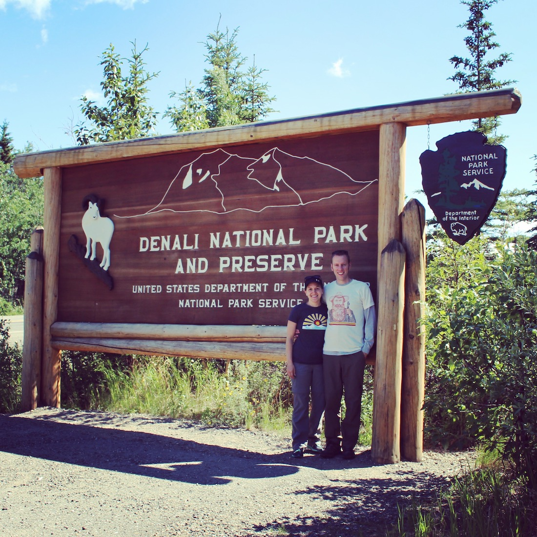 Park Chasers in front of the Denali National Park entrance sign.