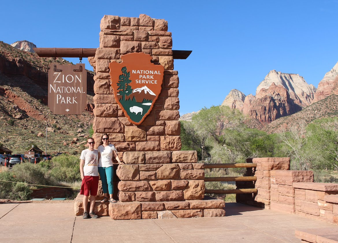 Park Chasers at the Entrance Sign to Zion National Park