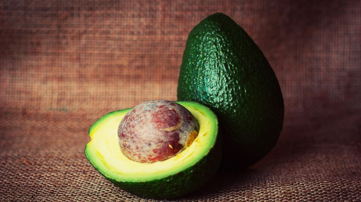 Cut avocado shown with brown background