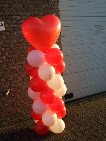 ballonnenpilaar met rood, witte ballonnenen een hartvormige ballon als topballon