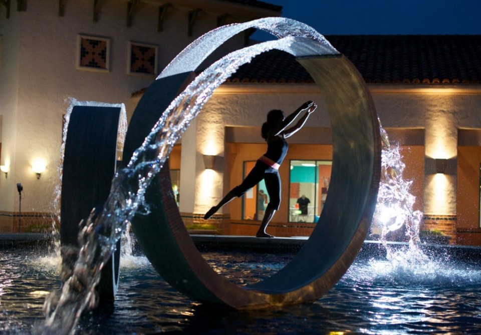 Barre pose picture at night viewed through the fountain