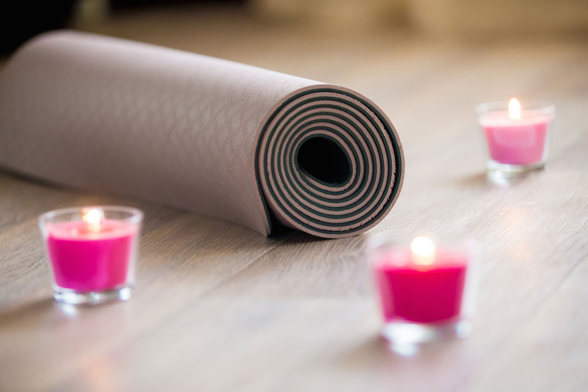 Passion barre lower cortisol levels blog image of rose-colored lighted pink wax candle and rolled brown pilates mat on the floor ready for workout. Close up. Healthy life, keep fit. Focus on mat