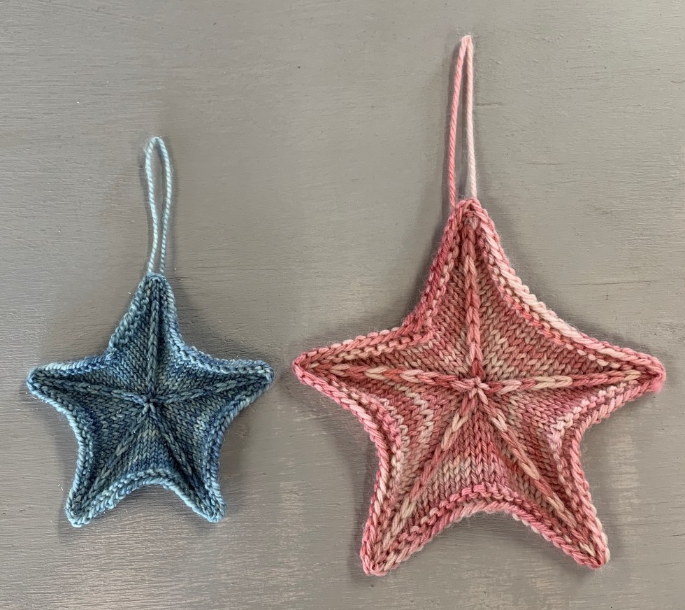 two knit stars - left in 4ply and right in 8ply