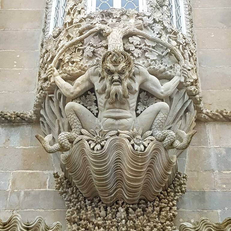 Merman gargoyle sitting in a clam shell looking down ferociously and guarding an entrance at Pena Palace.