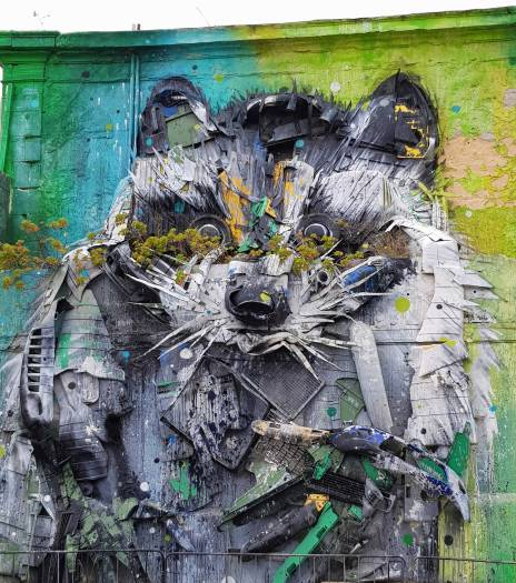 15 things to do in Lisbon - Badger street art on a wall made from waste materials like car bumpers and then spray painted.