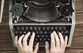 Writer typing with retro writing machine. View from above.