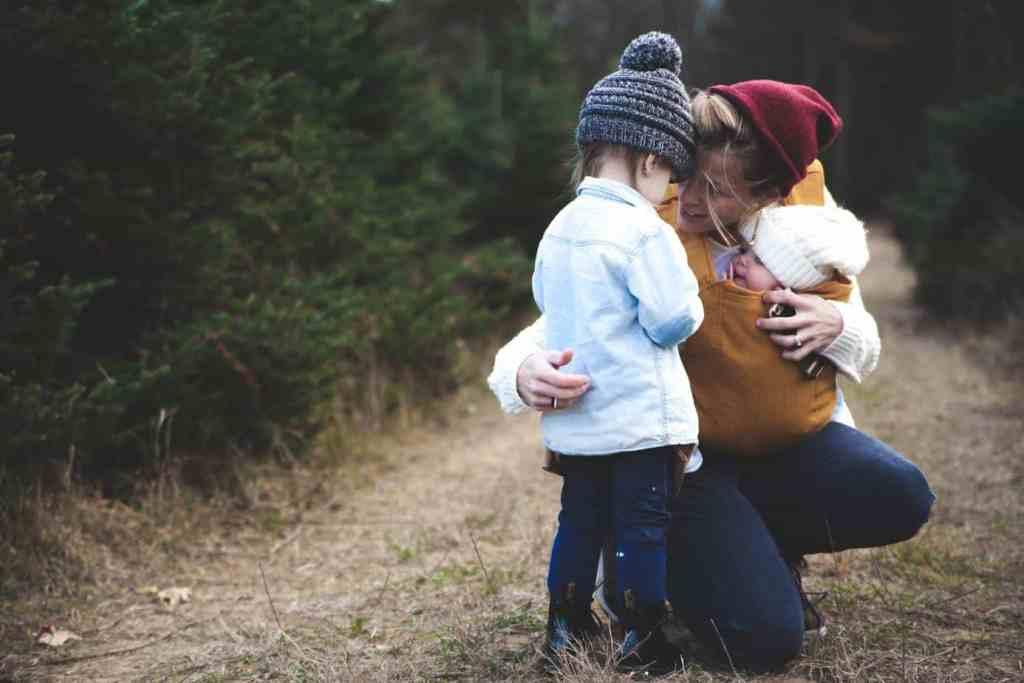 Mutter mit Baby im Tragetuch spricht auf Augenhöhe mit Kind