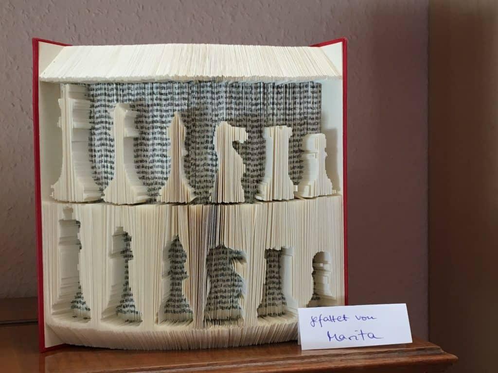 Gefaltetes Buch mit Schachfiguren