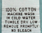 """Garment label with the text """"100% Cotton""""."""