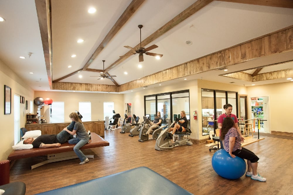 people doing physical therapy in large room