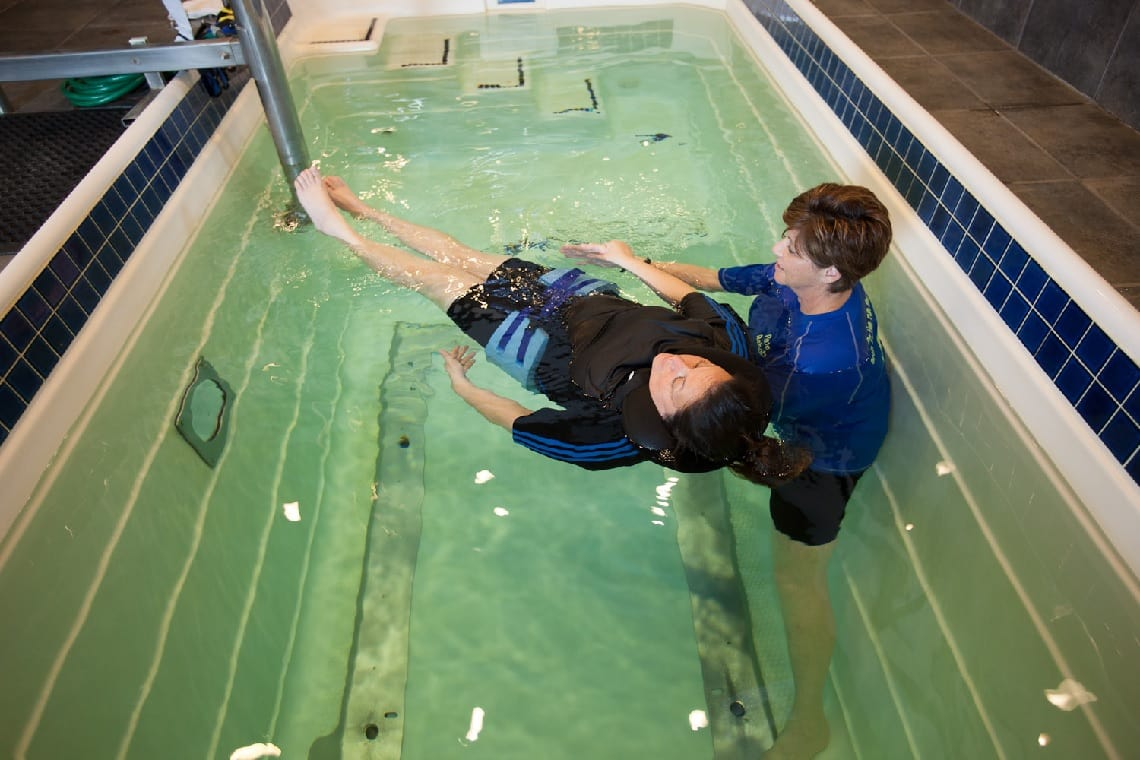 woman and therapist doing aquatic therapy
