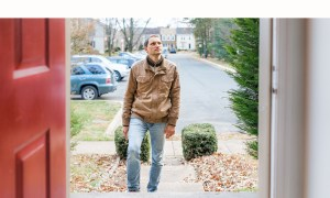 man in jeans walking in the front door of a home