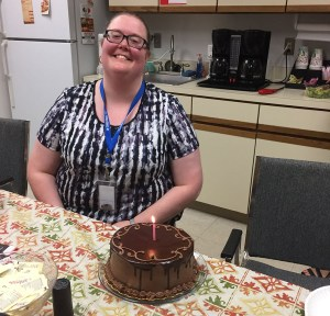 staff member with their birthday cake