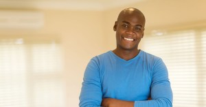black man smiling with arms folded