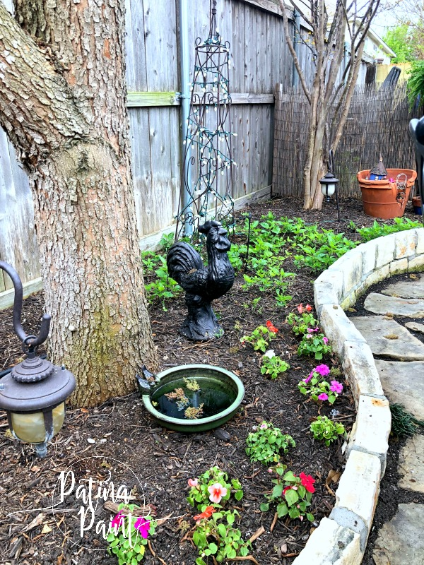 flower bed, tree, light birdbath, flowers rooster