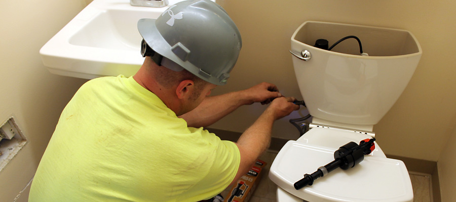 plumber working on bathroom toilet