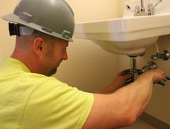 Plumber working on a bathroom sink