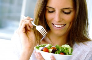 woman eats a salad for healthier hair