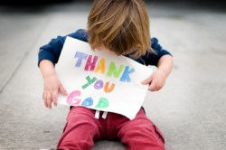boy with Thank You God sign