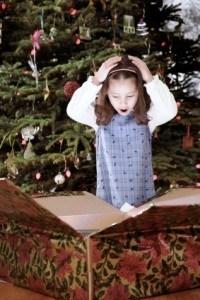 Hispanic girl opening Christmas gift