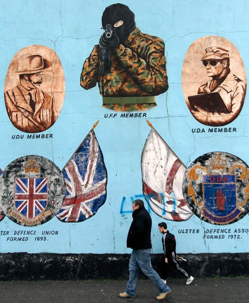 Father and Son walk past a mural in Belfast